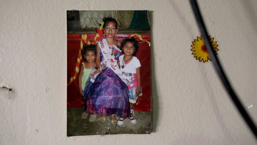A photo of Rubilia Sanchez's daughters Maquisha Perez, left, Ellie and Dashley, taken when they lived in Guatemala, hangs at their home in Los Angeles.