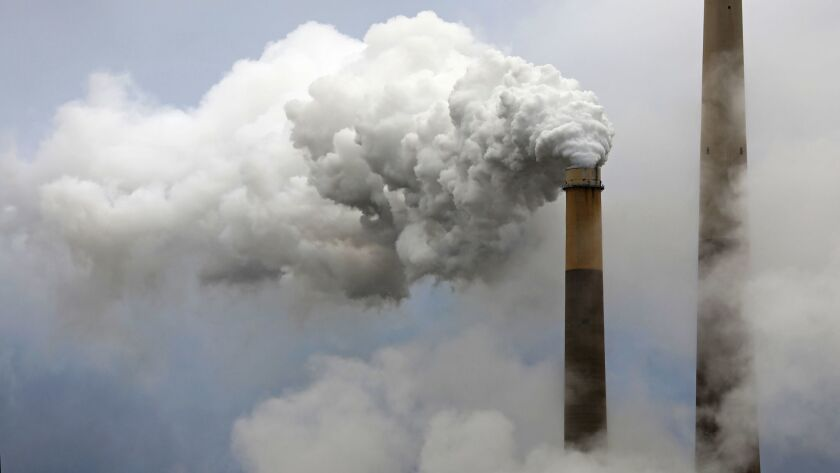 Steam rises from a stack at a coal-burning power station.
