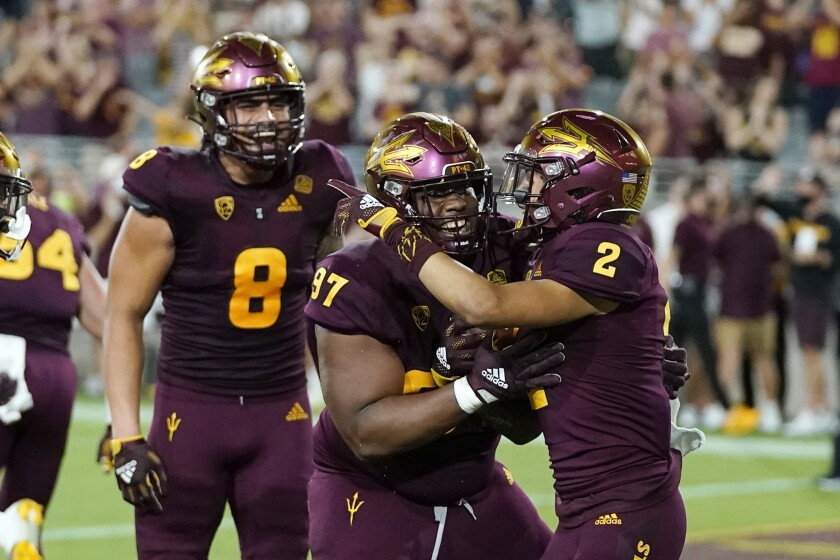 Arizona State defensive back DeAndre Pierce (2) celebrates his touchdown against Stanford with defensive lineman Shannon Forman (97) and linebacker Merlin Robertson (8) during the second half of an NCAA college football game Friday, Oct. 8, 2021, in Tempe, Ariz. (AP Photo/Ross D. Franklin)