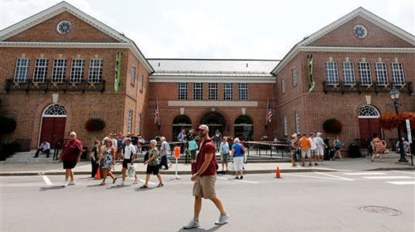 Fans walk outside the Baseball Hall of Fame and Museum in Cooperstown, N.Y. The Hall of Fame opened in 1939, the supposed centennial of the invention of baseball.