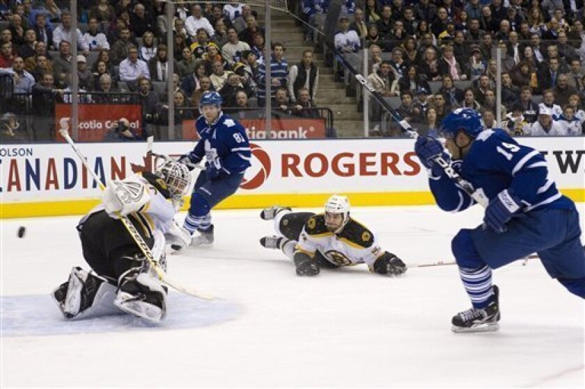 Boston Bruins goaltender Tim Thomas, left, defenseman Adam McQuaid, center right, and Toronto Maple Leafs' Phil Kessel (81) look on as Leafs' Joffrey Lupul scores his team's second goal during the second period of an NHL hockey game in Toronto on Wednesday, Nov. 30, 2011. (AP Photo/The Canadian Press, Chris Young)