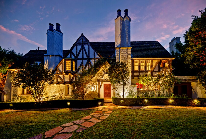 """The English Tudor Revival-style house was built in 1928 for the parents of Colleen Moore, a silent film actress who helped popularize the """"bob cut"""" hairstyle. Exquisitely restored and maintained, the two-story house retains its stained glass windows, coffered ceilings and grand fireplace mantles. A vaulted-ceiling foyer with a hand-carved staircase sits beyond the threshold of the Beverly Hills home, which is listed for $15.5 million. Outside, the grounds features English-style gardens, decorative fountains and two guest houses."""