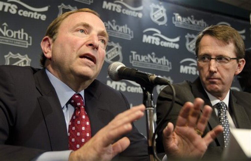 True North Sports and Entertainment Limited chairman Mark Chipman, right, looks on as NHL commissioner Gary Bettman speaks at a news conference, Tuesday May 31, 2011, in Winnipeg, Manitoba, announcing that the Atlanta Thrashers are moving to Winnipeg. (AP Photo/The Canadian Press, David Lipnowski)