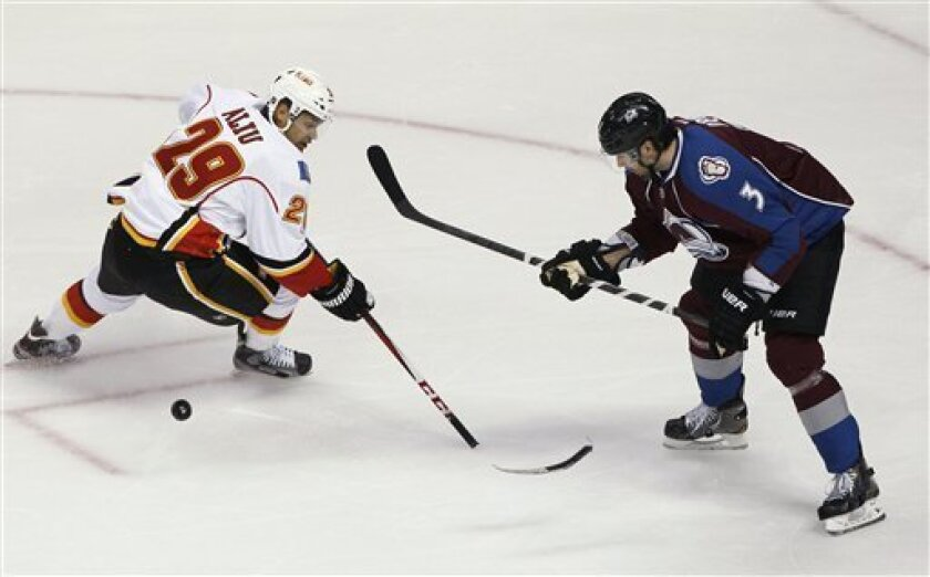 Calgary Flames right wing Akim Aliu loses control of the puck as the blade of his stick breaks off, while Colorado Avalanche's Ryan O'Byrne defends in the first period of an NHL hockey game in Denver on Thursday, Feb. 28, 2013. (AP Photo/David Zalubowski)