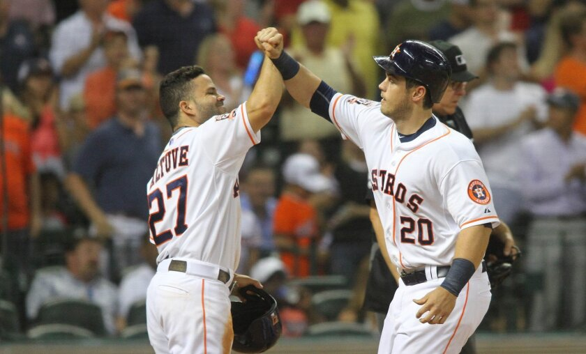 Houston Astros' Preston Tucker is greeted at the plate by Jose Altuve, left, after his two-run home run against the Boston Red Sox during the fifth inning of a baseball game Wednesday, July 22, 2015, in Houston. (AP Photo/Richard Carson)