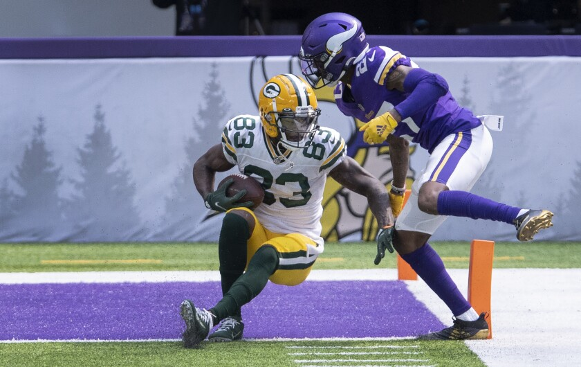 Green Bay Packers receiver Marquez Valdes-Scantling (83) catches a touchdown pass while being defended by Minnesota Vikings rookie defensive back Cameron Dantzler (27) in the second quarter of an NFL football game Sunday, Sept. 13, 2020, in Minneapolis. (Carlos Gonzalez/Star Tribune via AP)