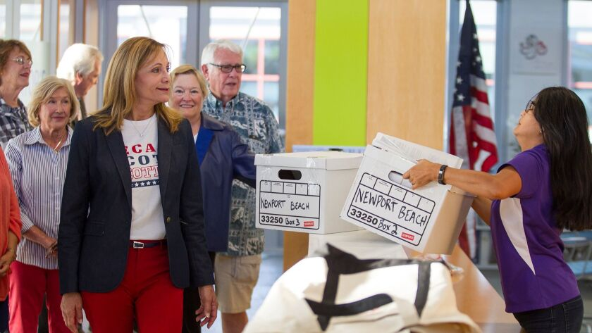 Lynn Swain, left, watches as Leilani Brown, the city clerk for Newport Beach, takes a box filled wit