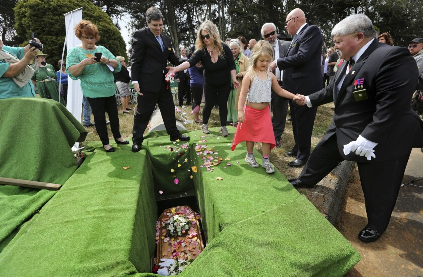 """Mourners including Lillet Gustavson, 6, toss rose petals on the lowered casket of """"Miranda Eve"""" during a graveside service in Colma, Calif., in June."""