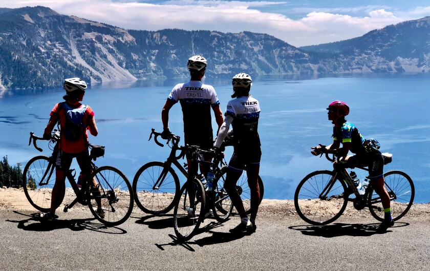 Cyclists on a Trek Travel trip gaze at the nearly 2,000-foot-deep Crater Lake from the Rim Road in Oregon.