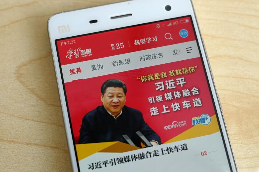 تصویر شی جین پینگ رئیس جمهور چین روی صفحه نمایش تلفن همراه با نمادهای چینی در اطراف آن.
