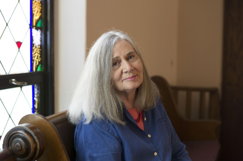 Marilynne Robinson sitting on a wood bench near a stained-glass window