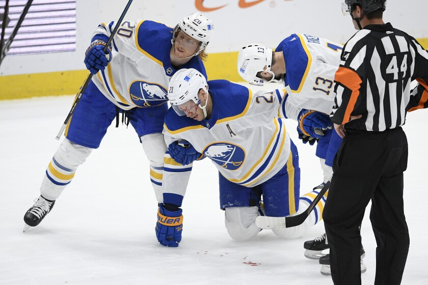 Buffalo Sabres right wing Kyle Okposo (21) is helped by center Cody Eakin (20) and left wing Tobias Rieder (13) after he was injured during the first period of the team's NHL hockey game against the Washington Capitals, Thursday, April 15, 2021, in Washington. (AP Photo/Nick Wass)