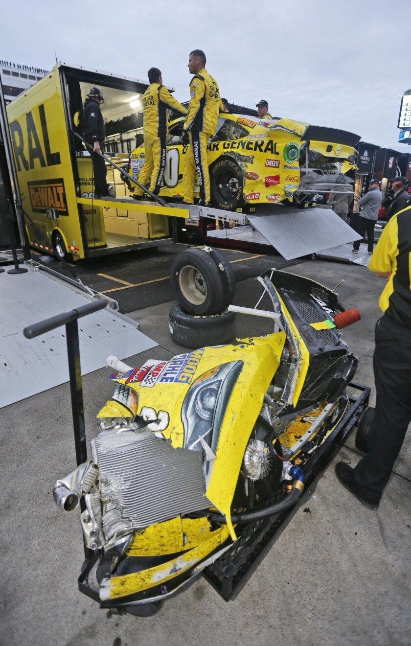 The pit crew for Matt Kenseth (20) loads his damaged car into the hauler after a crash with Joey Logano during the NASCAR Sprint Cup Series auto race at Martinsville Speedway in Martinsville, Va., Sunday, Nov. 1, 2015. (AP Photo/Steve Helber)
