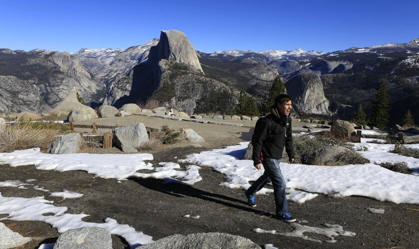 Darrell Carlis of Fresno hikes past patchy snow at Glacier Point in Yosemite National Park on Jan. 23. The arrival of a potentially powerful El Niño this coming winter could rejuvenate the thin Sierra snowpack.