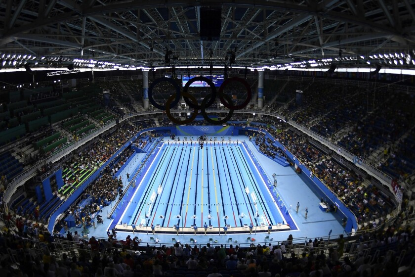Swimmers take part in a men's 400-meter individual medley preliminary heat on Saturday at the Olympic Aquatics Stadium.