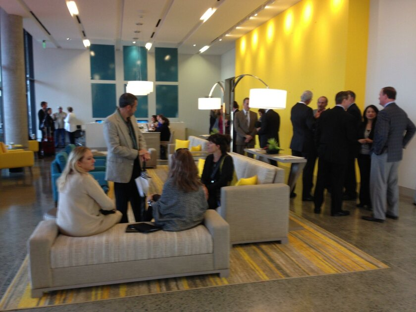 "SpringHill Suites and Residence Inn guests share a common lobby at the Lane Field hotel. The wall in the background, painted ""Cherry Yellow,"" reminds some guests of Lego bricks, hotel officials say."