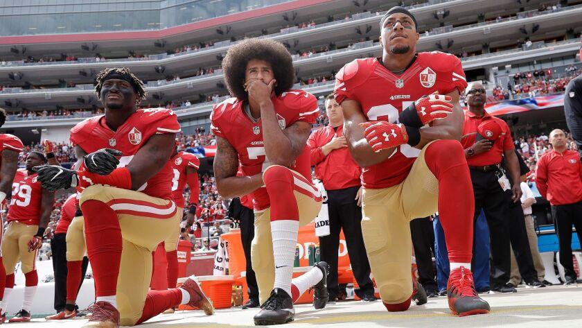 Colin Kaepernick (center) began the NFL national anthem protests.