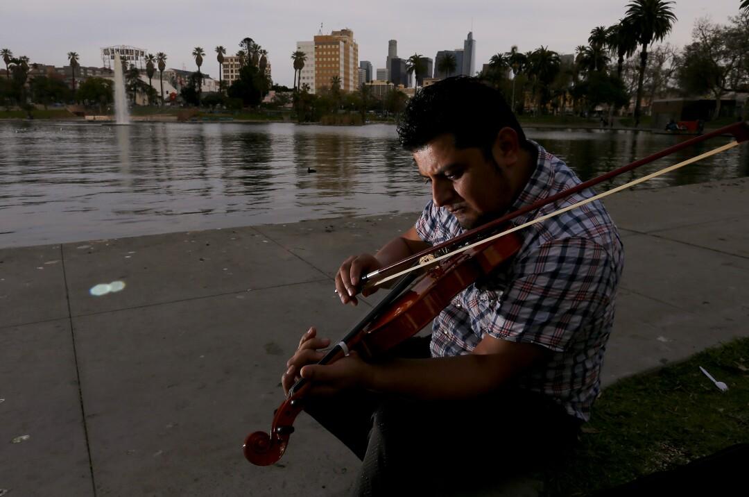 Osiel Ramirez plays violin at MacArthur Park in Westlake.