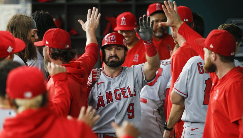 Los Angeles Angels' Adam Eaton (9) is congratulated in the dugout by teammates after hitting a solo home run during the third inning of a baseball game against the Texas Rangers, Thursday, Aug. 5, 2021, in Arlington, Texas. (AP Photo/Brandon Wade)
