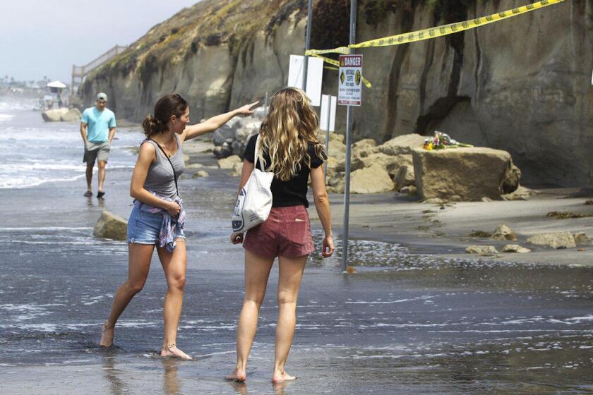 Varias personas observan las piedras de arenisca que se desprendieron en un acantilado y que causaron la muerte de tres mujeres en una playa en Encinitas, California. Encima de uno de los bloques fueron colocadas varias flores en memoria de las víctimas.