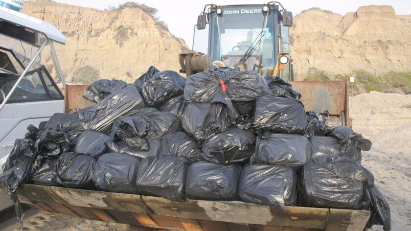 Border Patrol agents found 82 bundles of marijuana in large, black bags loaded in a 25-foot boat that washed ashore near San Clemente Monday, authorities said.