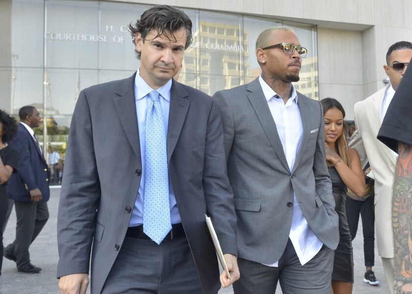 Chris Brown, right, leaves a Washington, D.C., courthouse with lawyer Danny Onorato on Tuesday morning. Brown took a plea deal related to his October assault arrest.