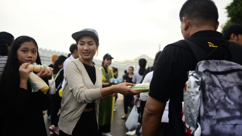 Volunteers distributing snacks and water to Thais mourning their king outside Bangkok's Grand Palace on Sunday.