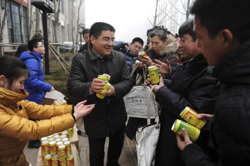 Chinese billionaire and philanthropist Chen Guangbiao, center, hands out cans of fresh air on a day of heavy air pollution at a financial district in Beijing in 2013.