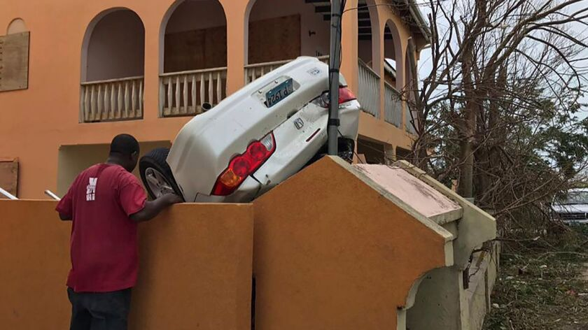 In this Sept. 6, 2017 photo, a man looks at a vehicle turned upside down by winds brought on by Hurr