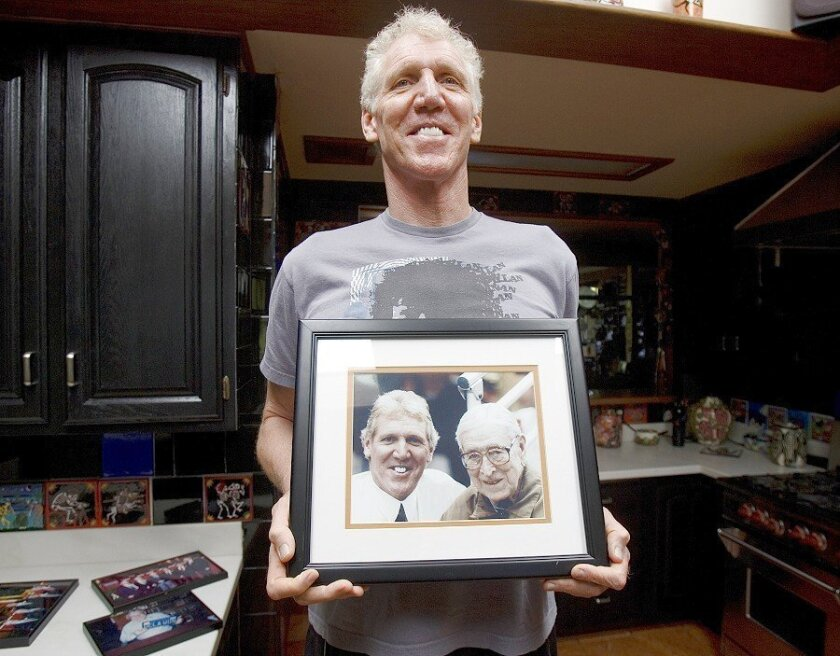 Bill Walton, in his San Diego home Saturday, holds one of his many photos of his college coach and lifelong mentor John Wooden.