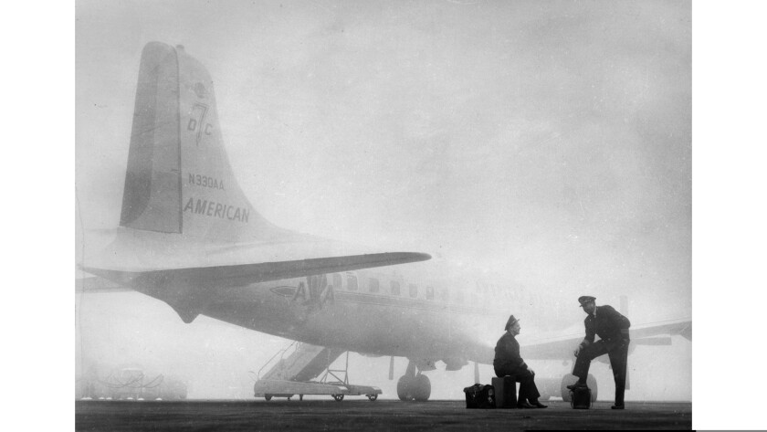 Jan. 29, 1958: American Airlines' flight engineer Frank Nusser, left, and Capt. Don Young wait by their aircraft for fog to lift at Los Angeles International Airport.