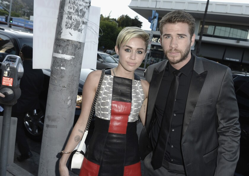 "Miley Cyrus and Liam Hemsworth attend the premiere of ""Paranoia"" in Los Angeles in August 2013."