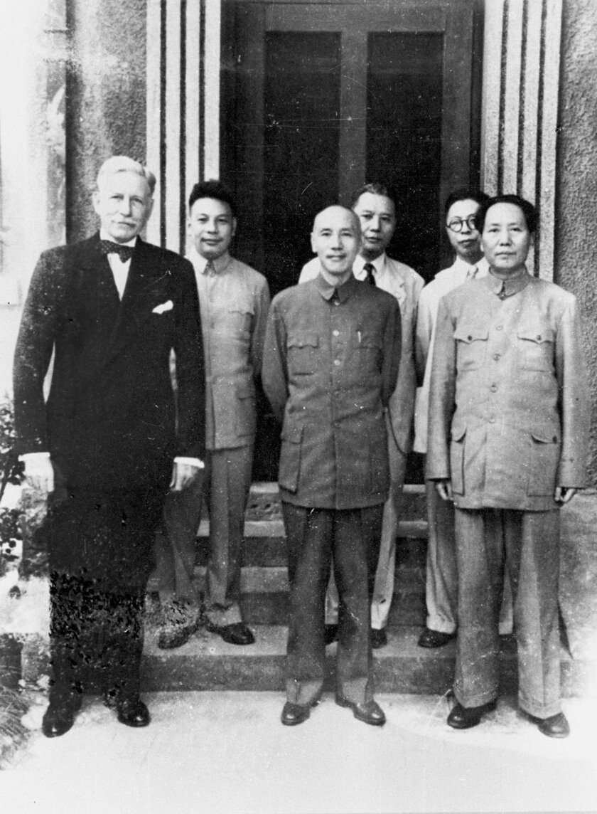 In this 1945 photo provided by the Central News Agency, China's Nationalist President Chiang Kai-shek, center, and his Communist rival Mao Zedong, right, stand together with US ambassador to China Patrick J. Hurley in Chongqing, China. Seventy years later, presidents of those two sides _ Taiwan's M