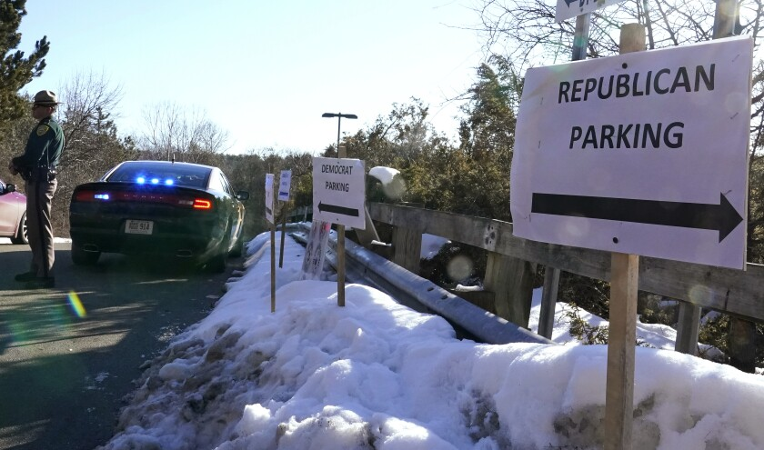 "FILE - In this Feb. 24, 2021, file photo, a sign directs Republican and Democrat legislators to their parking areas as a N.H. State Trooper watches the flow of traffic prior to a New Hampshire House of Representatives session held at NH Sportsplex, due to the coronavirus in Bedford, N.H. Amid calls to dial back hyper political partisanship, two letters are among the obstacles standing in the way. Republicans, including the lawyers who defended former President Donald Trump during last week's impeachment trial, routinely drop the ""i-c"" when referring to the Democratic Party or its policies. (AP Photo/Charles Krupa, File)"