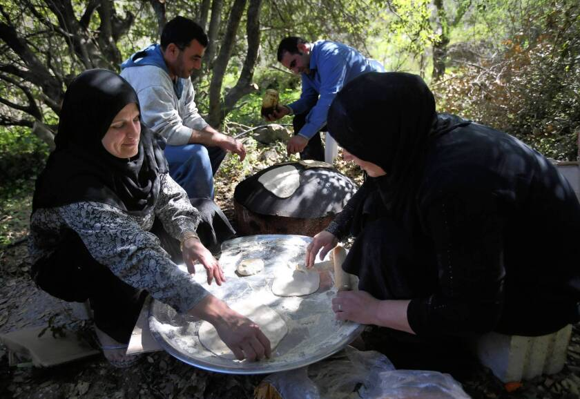 Syrian refugee women in Ketermaya village in Lebanon prepare flatbread for lunch for the visiting United Nations high commissioner for refugees, Antonio Guterres.