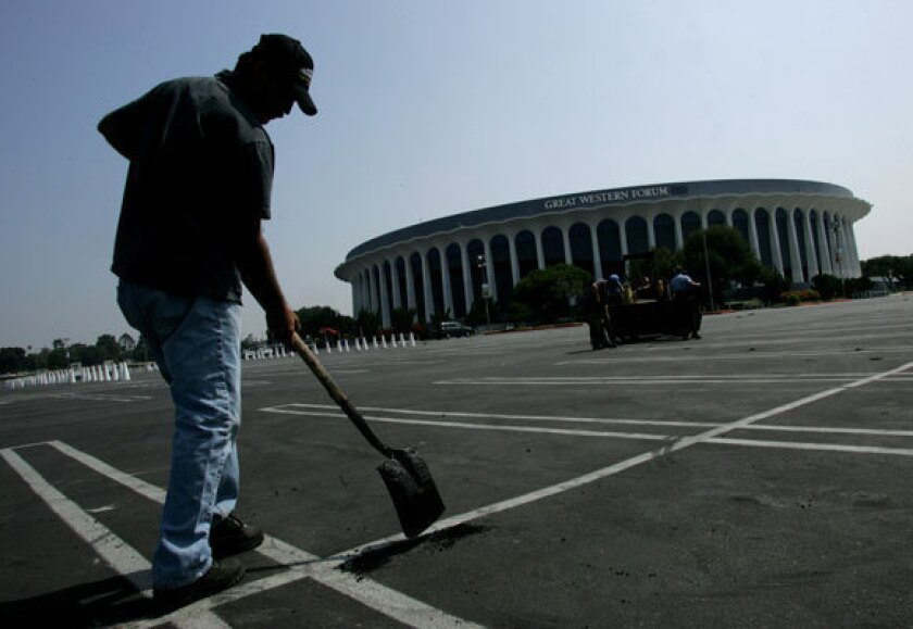 MSG, the new owner of the Forum, has paid $23.5 million for the facility and will start work this year on a $50-million renovation. The makeover is intended to turn the Forum into a top-flight concert hall and will take at least a year. Above, a worker fills potholes in the Forum's parking lot in 2005.