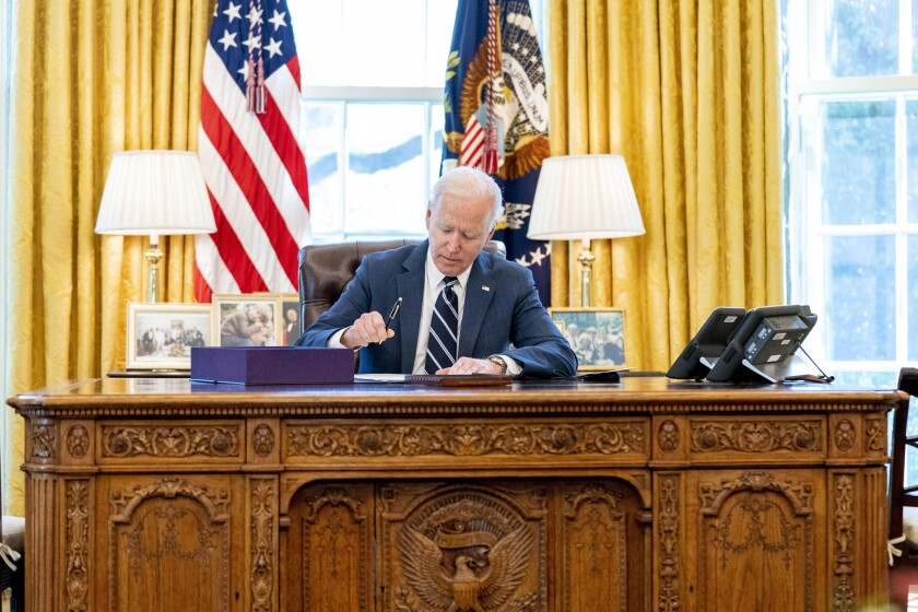 President Biden signs the American Rescue Plan, a coronavirus relief package, in the Oval Office on March 11.