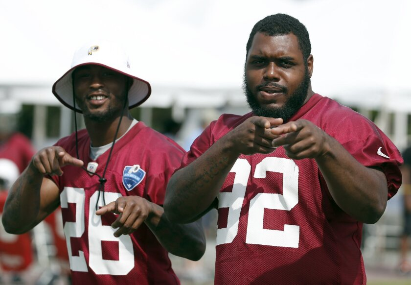 """FILE - In this July 27, 2014, file photo, Washington Redskins cornerback Bashaud Breeland, left, and defensive lineman Chris Baker gesture toward members of the media as they walk on the field during practice at the team's NFL football training facility in Richmond, Va. Chris """"Big Wiggle"""" Baker is the Redskins' life of the party. His other nickname is """"Swaggy."""" When """"Big Wiggle"""" gets a sack, the dance that follows is something to behold. (AP Photo/Alex Brandon, File)"""