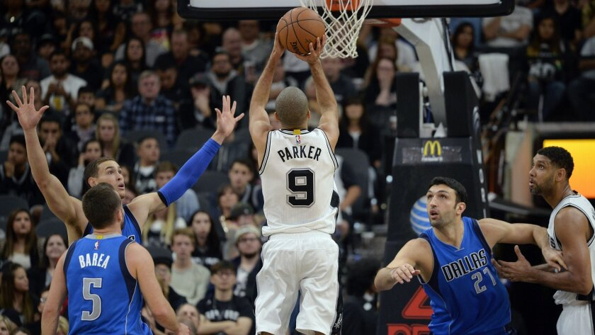 San Antonio Spurs guard Tony Parker (9), of France, shoots against Dallas Mavericks' Jose Juan Barea (5), Jeremy Evans (21) and Dwight Powell as Spurs' Tim Duncan, right, looks on during the first half of an NBA basketball game, Wednesday, Nov. 25, 2015, in San Antonio. (AP Photo/Darren Abate)