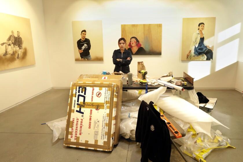 Shizu Saldamando stands amid boxes of art at Oxy Arts.