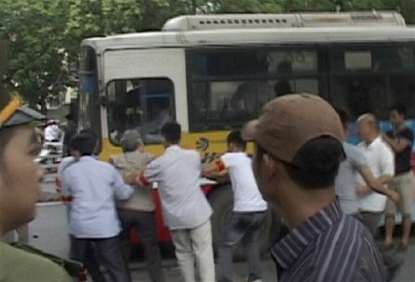 In this image made from video, a protester is dragged to a bus by police officers during an anti-China rally near Chinese Embassy in Hanoi, Vietnam, Sunday, July 10, 2011. More than a dozen demonstrators along with journalists covering the event for foreign news agencies were detained by police when they tried to assemble for the sixth straight Sunday to express outrage over an ongoing spat with China involving disputed territory in the South China Sea. (AP Photo)