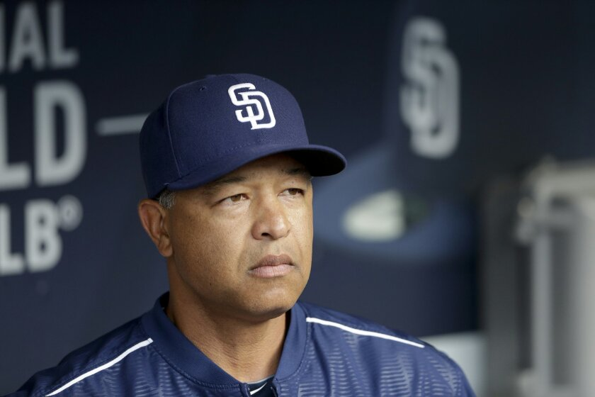 File- This June 15, 2015, file photo show San Diego Padres acting manager Dave Roberts looks on from the dugout before the Padres play the Oakland Athletics in a baseball game in San Diego. A person familiar with the decision has told The Associated Press that the Los Angeles Dodgers will name Roberts as their new manager. (AP Photo/Gregory Bull,File)