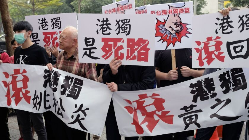 Protesters display anti-Hong Kong and anti-Taiwan independence banners outside a political forum hosted by Taiwan's New Power Party in Taipei on Saturday.