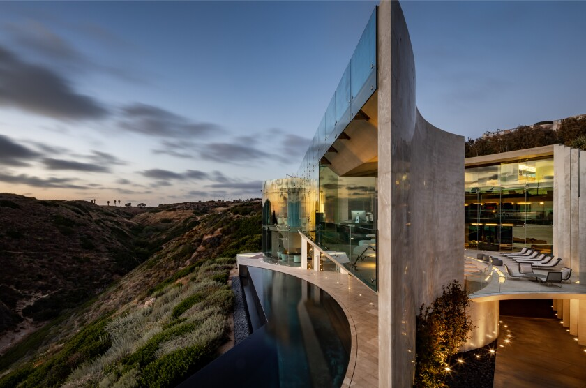 Built in 2007, the 11,500-square-foot modern mansion takes in sweeping ocean views from window-lined living spaces, rooftop terraces and a custom concrete courtyard.