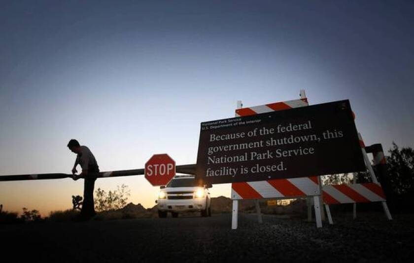 Park ranger Mike Shuman locks the western entrance to Joshua Tree National Park, closed due to the impasse in Congress over the federal budget.
