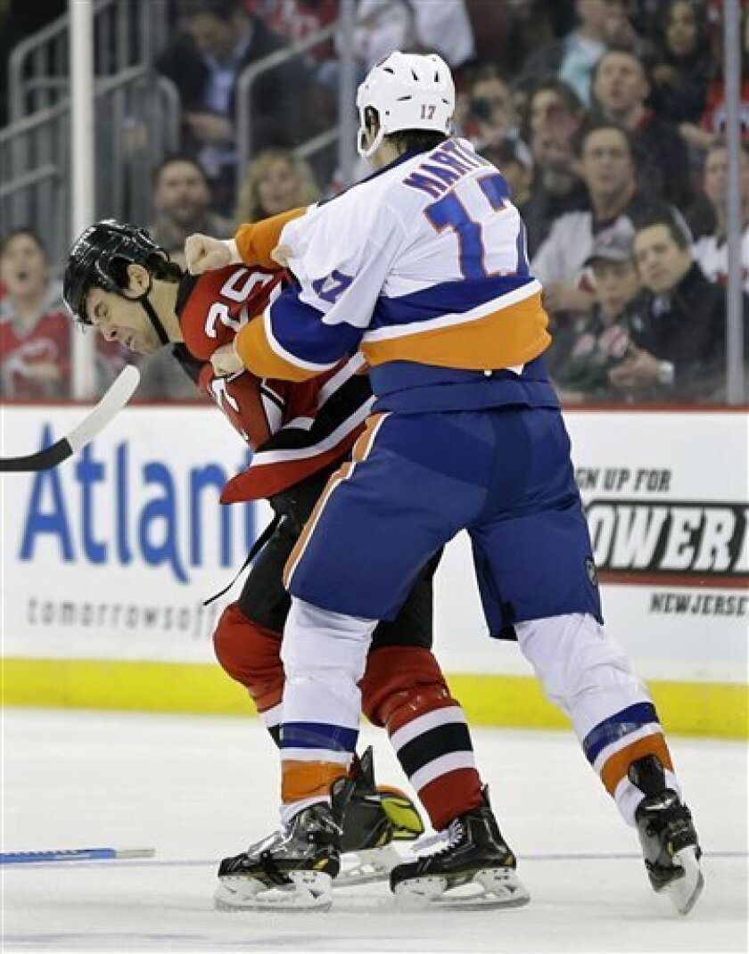 New York Islanders' Matt Martin (17) and New Jersey Devils Tom Kostopoulos (25) fight during the first period of an NHL hockey game Monday, April 1, 2013, in Newark, N.J. (AP Photo/Mel Evans)