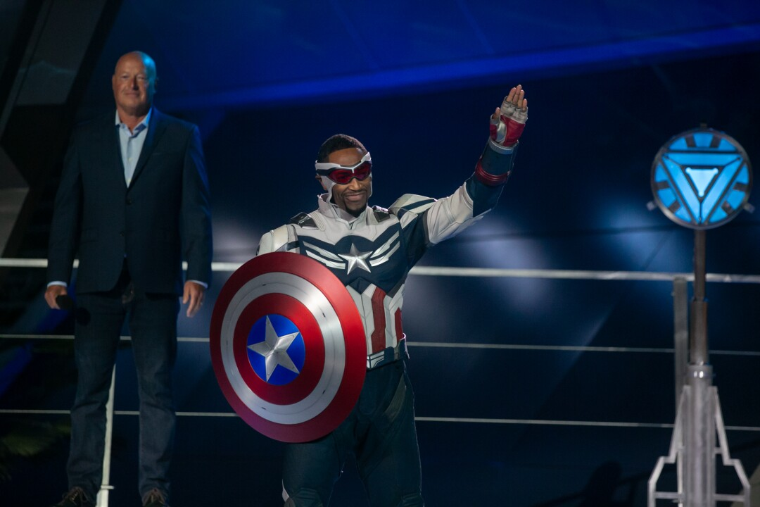 Captain America, holding his shield, waves.