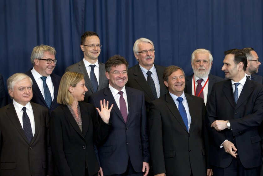 European Union High Representative Federica Mogherini, front second left, speaks with, Slovakian Foreign Minister Miroslav Lajcak, front center, and Slovenian Foreign Minister Karl Erjavec, front second right, prior to a group photo of EU foreign ministers at the EU Council building in Brussels on Monday, May 23, 2016. Libya has given the European Union a green light to begin training its coast guard, as increasing numbers of migrants leave the country bound for Italy. (AP Photo/Virginia Mayo)
