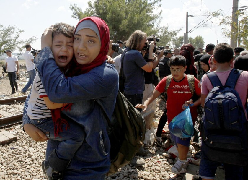 A woman migrant carries a boy who is crying, as they enter into Macedonia from Greece, on the border line between the two countries near southern Macedonia's town of Gevgelija, on Monday, Aug. 24, 2015. Thousands of migrants have poured into Macedonia and boarded trains and buses that are taking them a step closer to the European Union. Police are letting the migrants pass across the border Monday, directing them to the new transit center for migrants near the border line. (AP Photo/Boris Grdanoski)