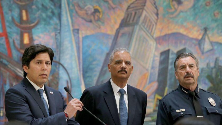Former U.S. Atty. Gen. Eric H. Holder Jr., middle, and Los Angeles Police Chief Charlie Beck, right, listen to Senate leader Kevin de León discuss the so-called sanctuary state bill on June 19 in Los Angeles.